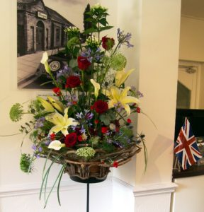 Beautiful standing flower arrangement of red roses, white lilies and foliage for HRH Prince of Wales visit to Morgan Cars