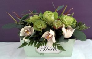 Vintage pink and green flowers arranged in a herb box