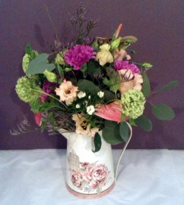 Relaxed pastel pink flowers and green foliage displayed in a vintage jugpink