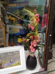 A floral display with small bird in the window of an art gallery