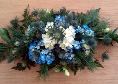 Blue and green funeral arrangement