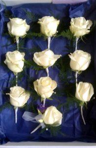 Ten white rose buttonholes rest in on blue satin.