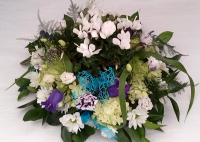 Delicate white and purple funeral display