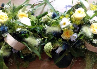Frothy green, white and yellow funeral flowers