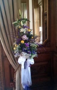 Wedding flowers on a stand in front of a mirror.