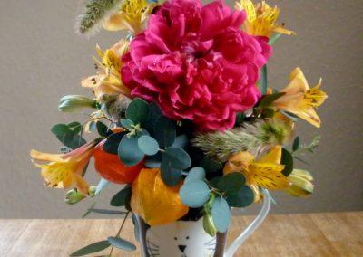 Bright yellow, orange and pink flowers displayed in a fun cat mug
