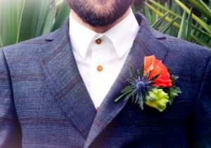 Purple thistle with orange and white rose bright wedding buttonhole worn in jacket from malvern florist Shrinking Violet Bespoke Floristry