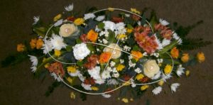 Orange, yellow, white and green funeral display. Gem stones placed in the centre of some flowers and white winter berries make a respectful statement