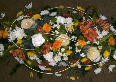 Orange, yellow, white and green funeral display