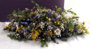 Green, yellow, white and blue wild-flower funeral display by Shrinking Violet Bespoke Floristry