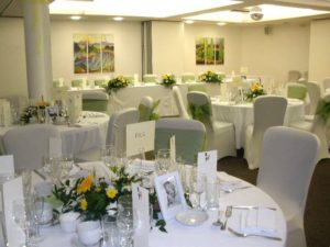 Yellow, white and green bespoke wedding flowers on reception tables by Shrinking Violet