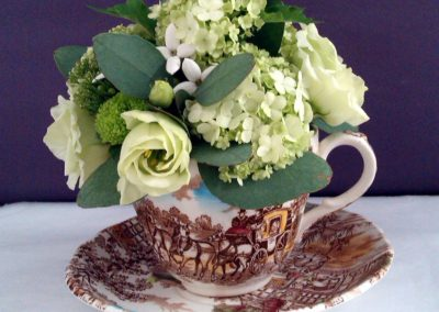 Green flowers in brown cup and saucer